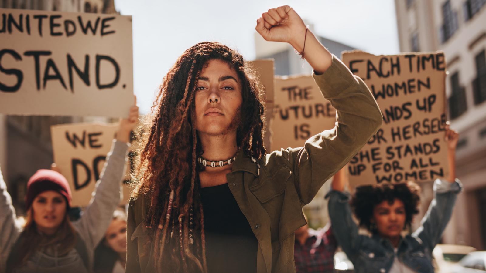 Frauen führen eine Gruppe von Demonstrierenden auf der Straße an.
